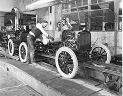 A Photograph of a Ford Assembly Line with a Worker Attaching a Gas Tank, circa 1923. (Photo by Fotosearch/Getty Images)